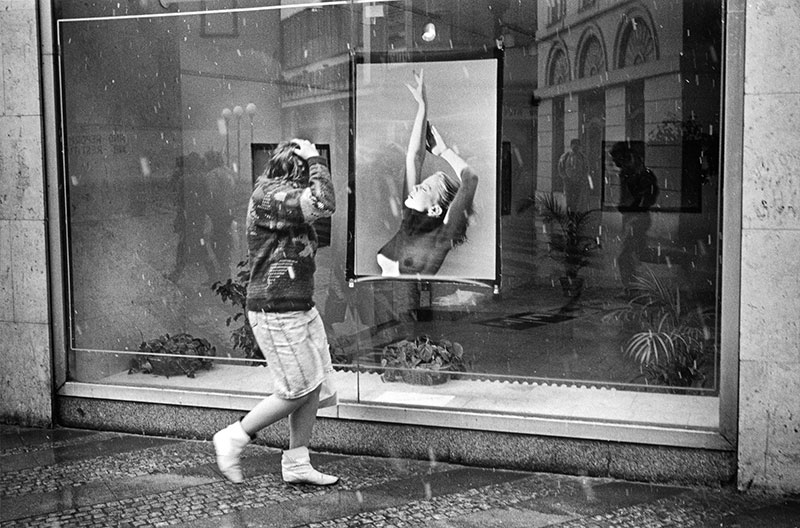 A woman walking in snow passes by a gallery window with a print of a nude model on display. Prague.